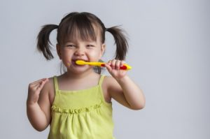 toddler smiling while brushing her teeth